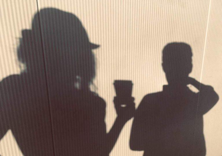 Na jasnej ścianie widać cienie dwóch osób od pasa w górę. Postać z lewej ma kapelusz i opadające na ramiona włosy, w ręku trzyma kubek. Druga postać mniejsza, z krótkimi włosami.