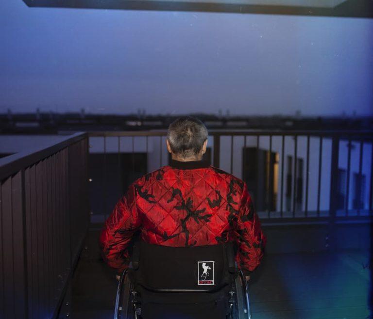 Pod ciemniejącym niebem siwiejący, krótko ostrzyżony mężczyzna zwrócony do nas tyłem siedzi na wózku na balkonie budynku. Patrzy w dal, od odległej rozmytej panoramy miasta oddzielają go barierki balkonu. Jego czerwona kurtka intensywnie kontrastuje z granatem nieba.