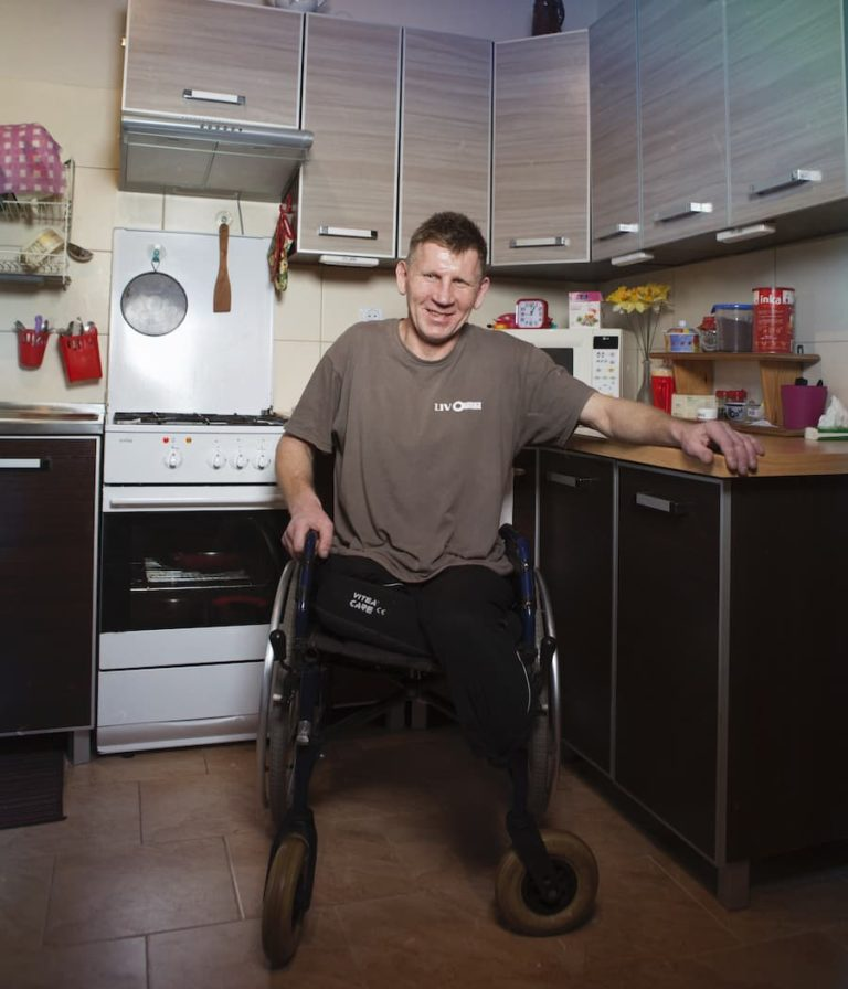 Zadowolony mężczyzna w średnim wieku, bez nóg siedzi na wózku w kuchni zwrócony twarzą do nas, lewym ramieniem opiera się swobodnie o blat kuchenny, druga ręka spoczywa na obręczy koła, za nim zabudowana narożna kuchnia, schludna i uporządkowana.