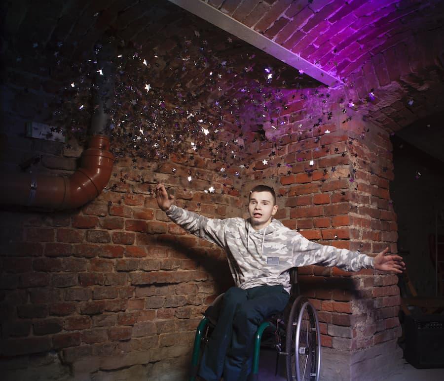 Nastolatek na wózku we wnętrzu budynku ze starej cegły, wózek ustawiony w narożu, nad nim łukowate sklepienie, po prawej ciemne przejście do środka. Chłopak patrzy przed siebie i szeroko rozkłada ramiona. Z góry sypie się na niego srebrno-lśniące gwiezdne konfetti.