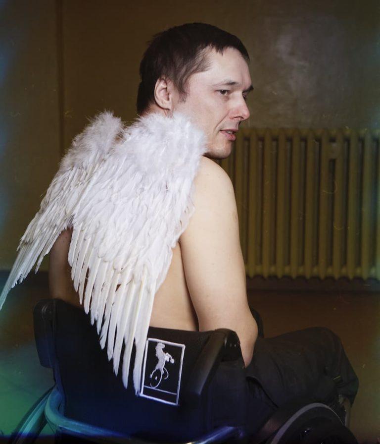 Mężczyzna na wózku siedzi w pomieszczeniu. Jest zwrócony do nas tyłem, ale z widocznym profilem twarzy. Na nagich plecach ma białe anielskie skrzydła.