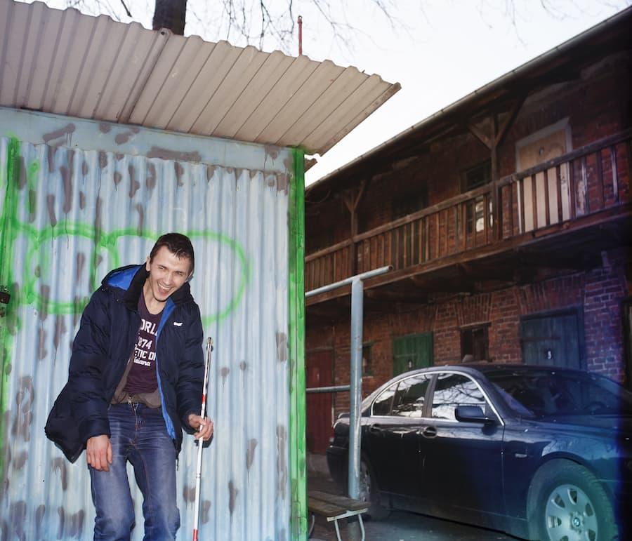 Pod obdrapaną wiatą z blachy falistej stoi młody mężczyzna i aż skręca się ze śmiechu, w lewej dłoni trzyma laskę niewidomego. Po prawej podwórkowy trzepak, samochód osobowy, w tle jednopiętrowy budynek gospodarczy z cegły i z drewnianą galerią.