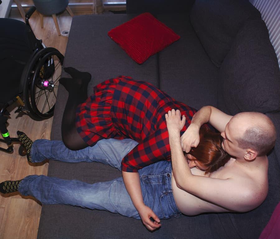 Perspektywa z góry na sparaliżowanego mężczyznę, który w pozycji półleżącej na sofie, nieporadnie obejmuje ramionami wtuloną w jego nagi tors kobietę. Ona skulona przywiera do niego całym ciałem, jej twarz jest częściowo przysłonięta włosami. Po lewej stronie stoi jego wózek.