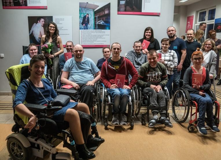 Grupa ok. 10 osób na wózkach inwalidzkich i kilka osób pełnosprawnych w sali wystawowej. Uśmiechnięci stoją przodem do obiektywu. Za nimi wielkoformatowe zdjęcia z tekstami wierszy.